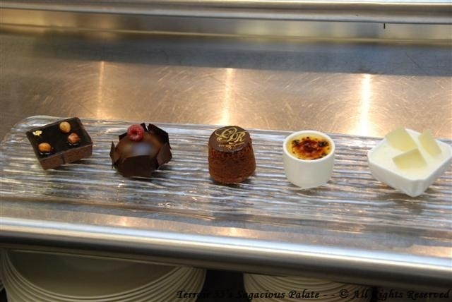 Dessert medley: Hazelnut praline tart, chocolate sphere with chocolate mousse and raspberry preserves, chocolate molten lava cake, vanilla creme brulee and white chocolate mousse.